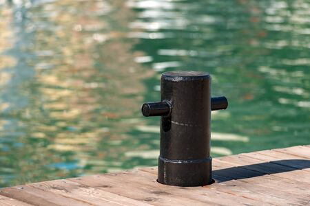 black moor: Detail of old and black mooring bollard on the wooden pier with water in the background