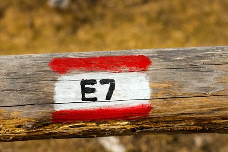 wooden trail sign: European Trail Sign E7 Lisbon Portugal - Constance Lake Romania on a wooden pole