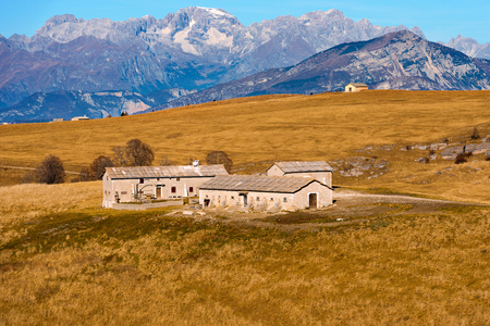 farmhouses: Typical farmhouses Malghe in Lessinia Verona, Italy for the breeding of cows, in the background the Brenta Dolomites. Editorial