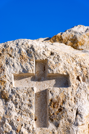 crucify: White limestone with engraved cross, the symbol of Jesus Christ. Against the blue sky Stock Photo