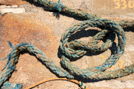 threadbare: Detail of weathered nautical rope, blue and orange, on the pier in the harbor