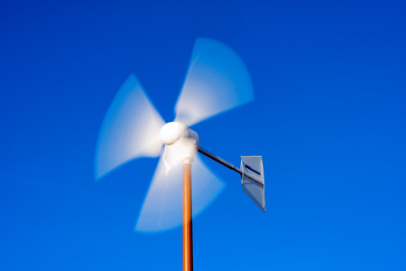energy sources: Close up of a wind turbine with blades in motion on clear blue sky