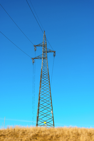 powerline: Electricity pylon with power lines against blue clear sky in mountain