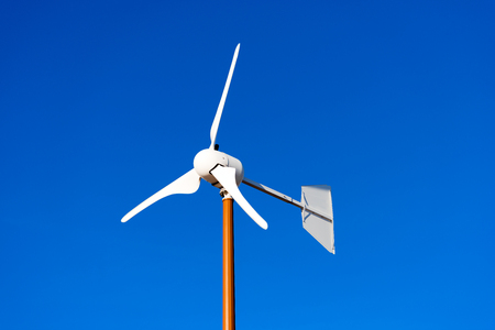 Close up of a small wind turbine with blades on clear blue sky
