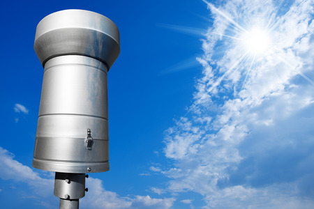 pluviometro: Weather station with metallic rain gauge on a blue sky with clouds and sun rays