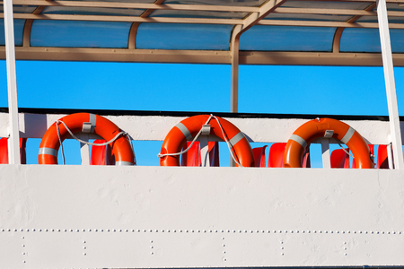 buoys: A row of red and orange life buoys on the deck of a passenger ship