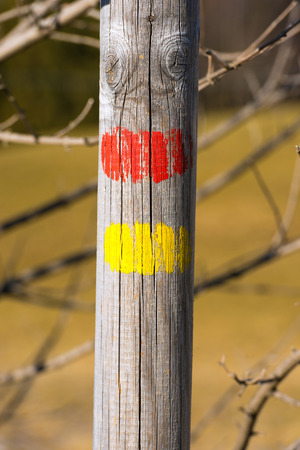 wooden trail sign: Red and yellow trail sign on a wooden pole, Italian Alps