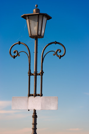lamp post: Old vintage lamp post with blank sign board and cobwebs on a clear blue sky