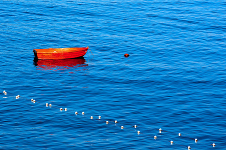 rowing boat: Red rowing boat moored in a harbor to a red buoy on the blue waves Stock Photo
