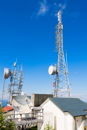 transmit: Communication towers with a blue sky in mountain. Used to transmit television and radio signals Stock Photo