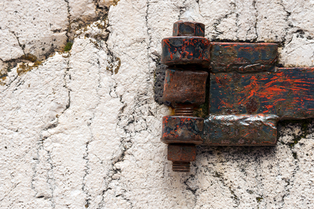 hinge: Detail of an old rusty hinge with big bolts on a white rock