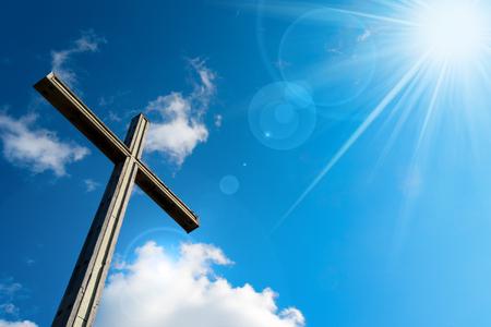 christian faith: Wooden christian cross on blue sky with clouds and sun rays