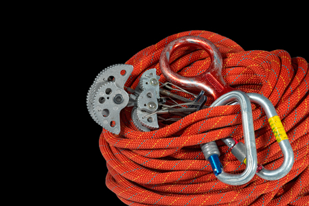 descender: Rock climbing equipment with climbing cams friends, climbing descender eight descender and a carabiner. Isolated on black background Stock Photo
