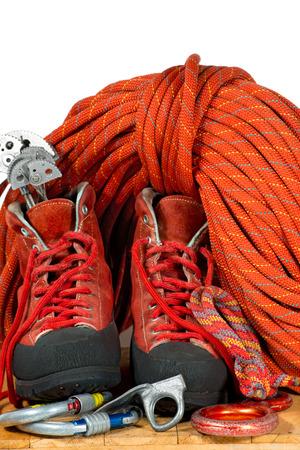 escalada: Equipo de la escalada con botas de monta�ismo, escalada, levas de descenso, mosquetones, pitones y una cuerda roja. Aislado en el fondo blanco Foto de archivo