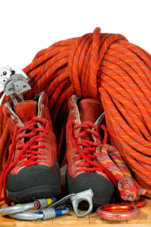 cam gear: Rock climbing equipment with mountaineering boots, climbing cams, descender, carabiners, piton, and a red rope. Isolated on white background