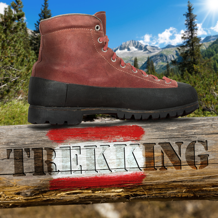 wooden trail sign: Old red and black trekking boot on a wooden pole with red and white trail sign and text Trekking. In the background blurred mountain landscape