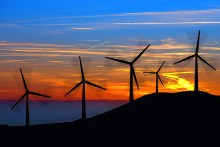 Five silhouettes of wind turbines in mountain with a beautiful sunset