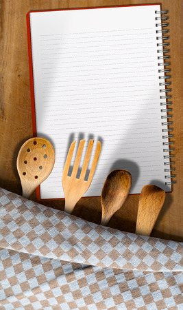 ladles: Open notebook for recipes or menu on an wooden table with checkered tablecloth and wooden kitchen utensils, fork, spoons and ladles