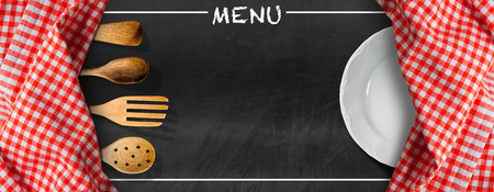 Blackboard with red and white checkered tablecloth, text Menu, wooden kitchen utensils and white empty plate. Template for a food menu