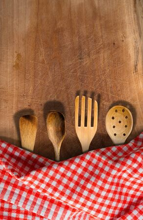 ladles: Four wooden kitchen utensils, fork, spoons and ladles on a wooden table with red and white checkered tablecloth Stock Photo