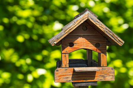 Old wooden birdhouse on a green blurred background