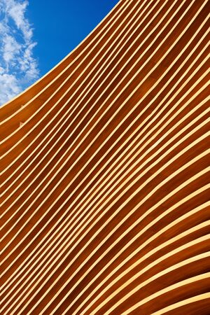 panelling: Close up of a modern wooden architecture on a blue sky with clouds