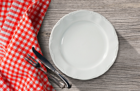 pic nic: Empty white plate on a table in pine wood with silver cutlery, fork and knife, and a red and white checkered tablecloth Stock Photo