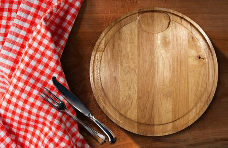 Empty round cutting board on a wooden table with silver cutlery, fork and knife, and a red and white checkered tablecloth Stock Photo