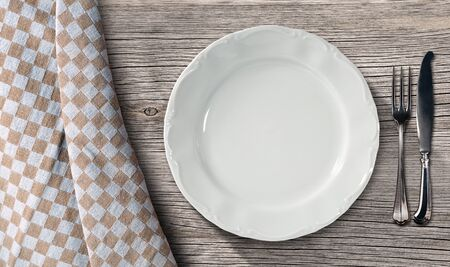 pic nic: Empty white plate on a table in pine wood with silver cutlery, fork and knife, and a brown and white checkered tablecloth Stock Photo