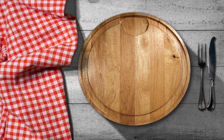 pic nic: Empty round cutting board on a wooden table with silver cutlery, fork and knife, and a red and white checkered tablecloth Stock Photo