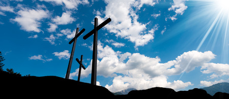 crucify: Silhouette of three crosses against a blue sky with clouds and sun rays. Carisolo Trentino Italy