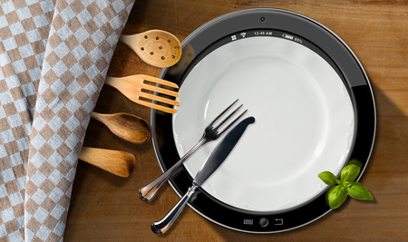 silver cutlery: Round tablet computer in a kitchen with silver cutlery and wooden kitchen utensils on a wooden table with checkered tablecloth