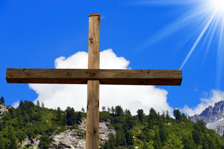 crucify: Wooden christian cross in mountain, Italian Alps, with blue sky, clouds and sun rays