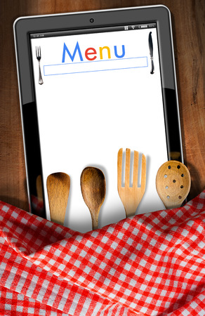 ladles: Tablet computer with text Menu in the screen, on a wooden cutting board, checkered tablecloth and wooden kitchen utensils, fork, spoons and ladles