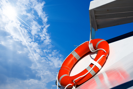 passenger ship: Detail of an orange lifebuoy on a white passenger ship with blue sky, clouds and sun rays