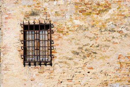 Detalle de una ventana con un viejo y oxidado rejilla en una pared vieja con los ladrillos. San Gimignano, Siena, Toscana, Italia
