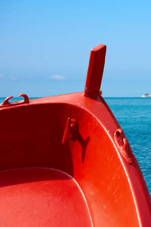 prow: Detail of a wooden red prow of a rowing boat with sea in background. Liguria, Italy Stock Photo