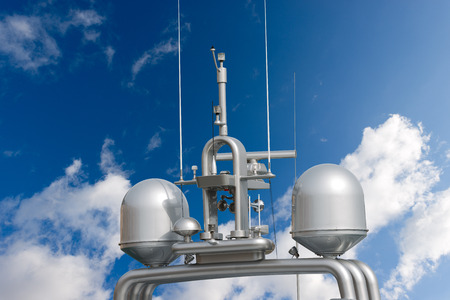 superstructure: Detail of luxury grey yacht with navigation equipment, radar and antennas on blue sky with clouds Stock Photo