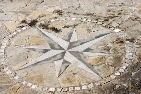 puntos cardinales: suelos de piedra con rosa 8 direcciones. Un muelle en el puerto de Liguria, Italia Foto de archivo