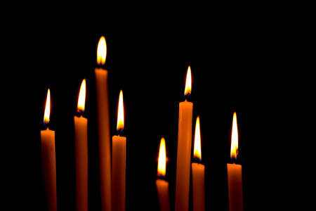 pious: A group of warm glowing candles on dark background