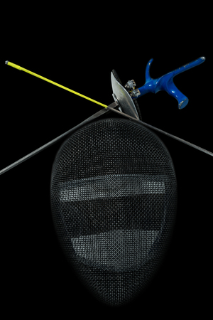 fencing foil: Fencing foil equipment. Two fencing foils with pistol grip and tip, and a fencing mask. Isolated on black background