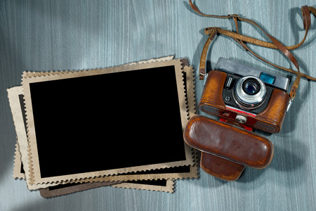 old desk: Old and vintage camera with leather case and a stack of old vintage photo frames on a desk with shadows Stock Photo
