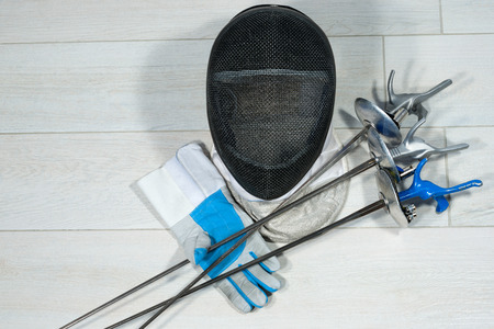 Fencing foil equipment. Three fencing foils with pistol grip (sporting weapon), a fencing mask and a blue and white glove on floor.