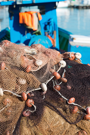 commercial fishing net: Fishing nets with ropes and floats in the harbor, in the background, blurred fishing boats