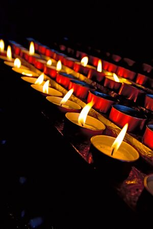 votive: A group of blurred and red votive candles in the darkness of a church Stock Photo