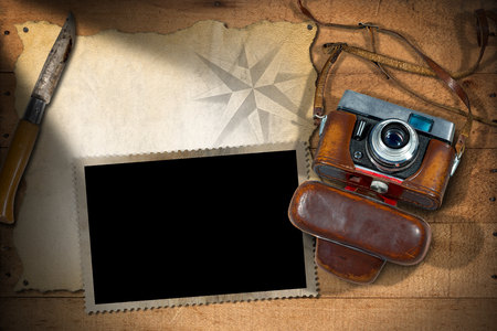 adventurous: Old and vintage camera with leather case, empty parchment, photo frame and a pen knife. Template for adventurous travels