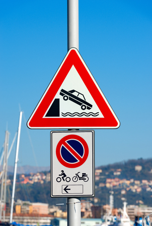 unprotected: Detail of a warning triangle traffic sign of unprotected quayside and no parking for motorcycles and scooters - Italy, Europe