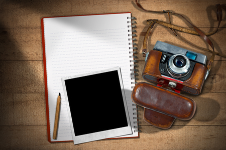 case: Viejo y cámara de la vendimia con el caso de cuero, cuaderno vacío con el lápiz y un marco de foto instantánea en una mesa de madera
