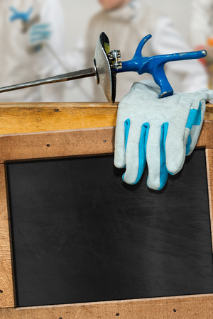 fencing foil: Empty chalkboard with wooden frame, a detail of a fencing foil, glove and blurred fencer. Template for fencing sport
