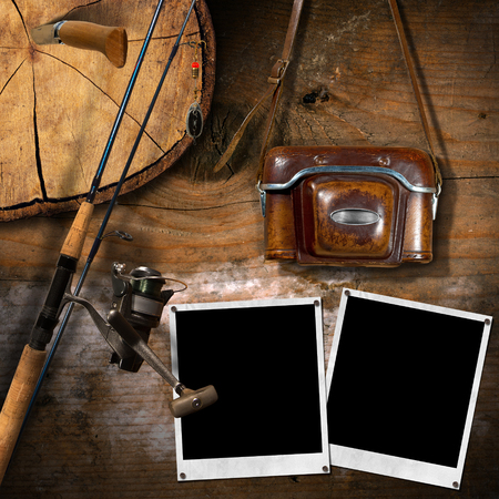 temperino: Fishing tackle, vintage camera with leather case, two empty instant photo frames and a penknife on a wooden wall